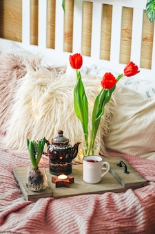 Wooden tray with tea and spring flowers on a cozy bed, vertical photo. high quality photo