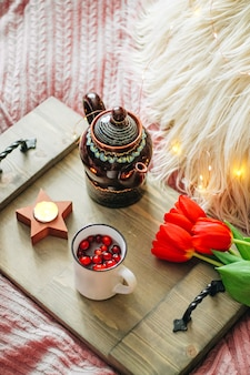 Wooden tray with tea and tulips on a cozy bed, vertical photo. high quality photo