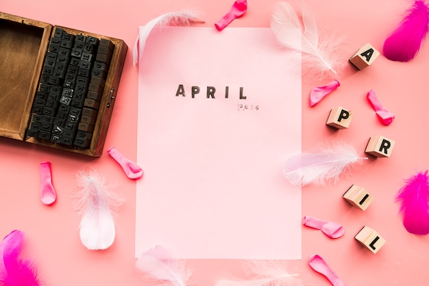 Wooden typographic blocks; balloons; feather; april blocks and april stamp on white paper against pink backdrop