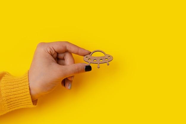黄色の背景の手に木製ufo