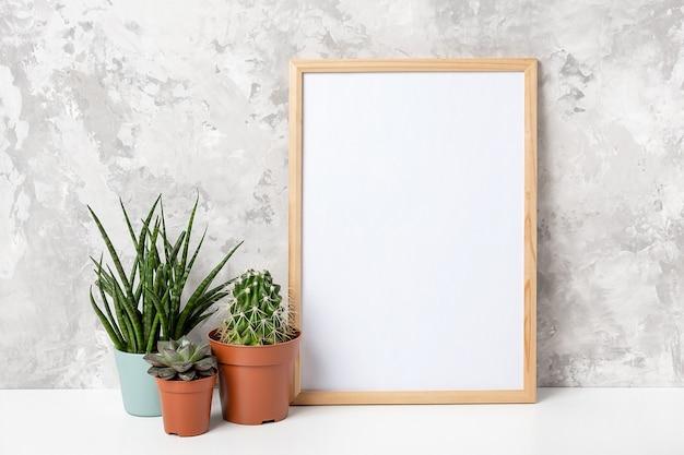 흰색 빈 카드가 있는 나무 수직 프레임과 회색 콘크리트 벽 배경에 있는 테이블에 있는 냄비에 녹색 화초 꽃. 디자인, 텍스트에 대한 모형 템플릿입니다.