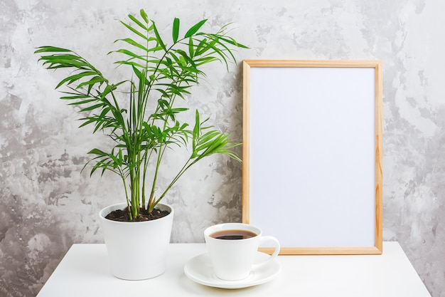 Wooden vertical frame with white blank card, cup of coffee and green exotic palm flower in pot on table on gray concrete wall