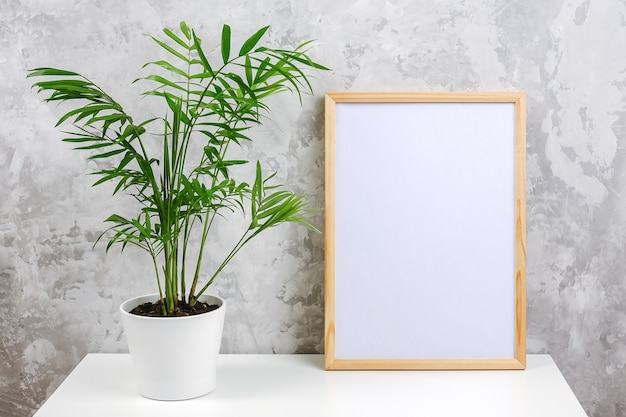 Wooden vertical frame with white blank card and green exotic palm flower in pot on table on gray concrete wall