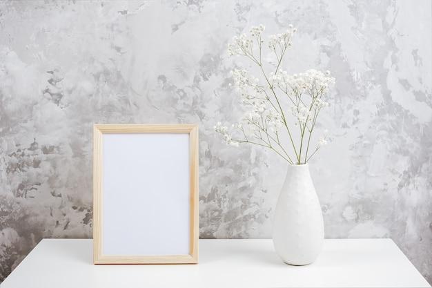 木製の垂直の白い空のフレームと灰色のコンクリートの壁にテーブルの上の花瓶に白い小さな花カスミソウの花束