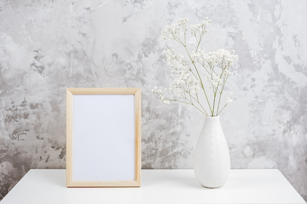Wooden vertical white empty frame and bouquet of white small flowers gypsophila in vase on table on gray concrete wall