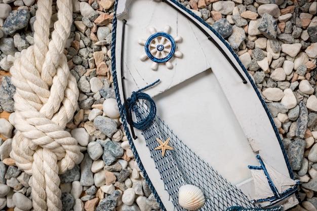 小石の上に横たわるボートの形をした木製のビューフレーム