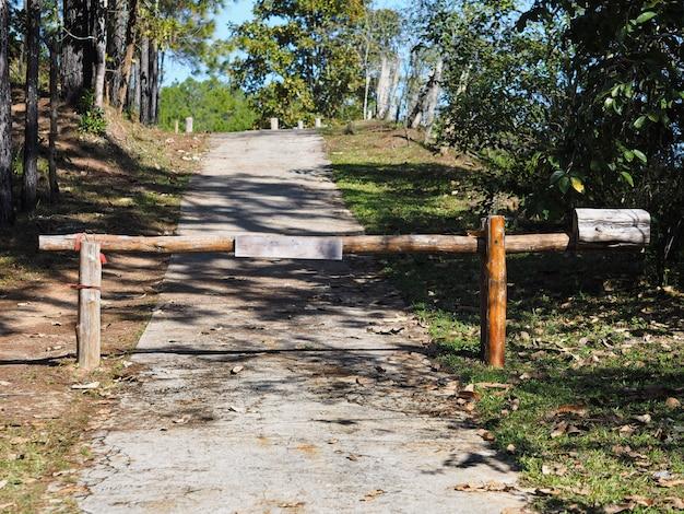 Деревянный старинный барьер у въезда на лесную дорогу.