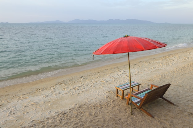 Wooden vintage table set with red umbrella and seascape space