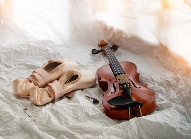 The wooden violin put beside ballet shoes, warm light tone, blurry light around
