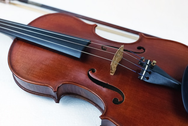 Wooden violin put on white background, in front of blurred bow, show front side of string instrument
