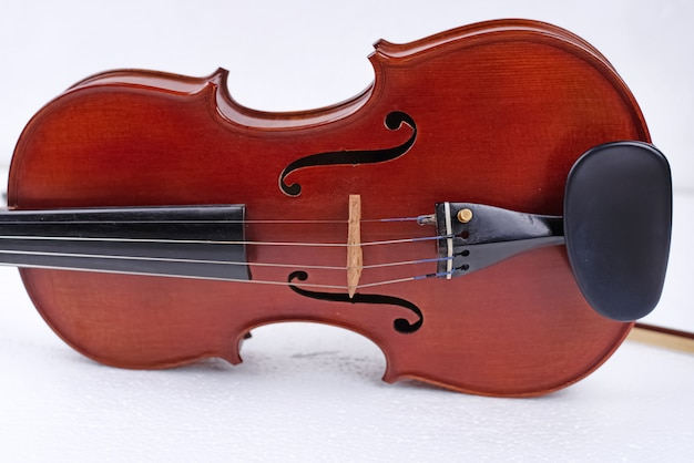 Wooden violin put on white background, show front side of string instrument