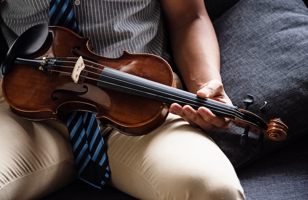 The wooden violin was holding by human hand