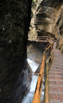 계단식 폭포 위의 다리 역할을 하는 나무 산책로