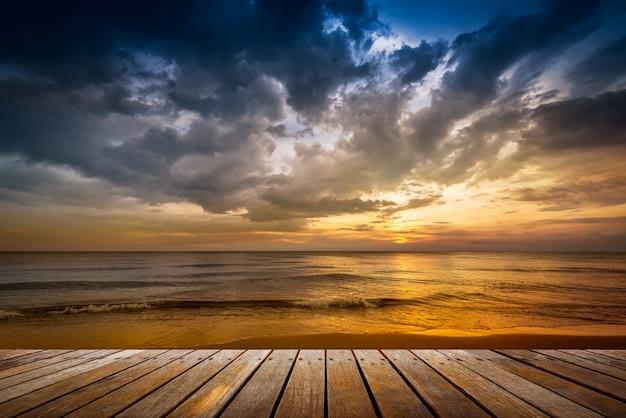 日没時のビーチで木製の通路