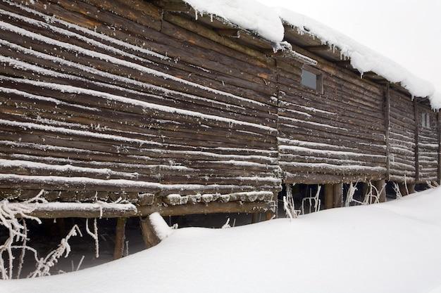 Деревянный стеновой дом на зимней вершине горы