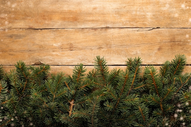 Деревянная стена с ветвями елки и снегом. рождественское понятие. баннер. скопируйте пространство.