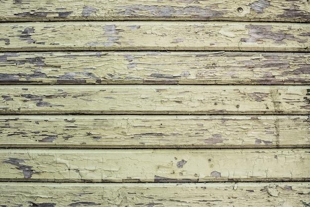 ひびの入った古い緑色のペンキと木製の壁