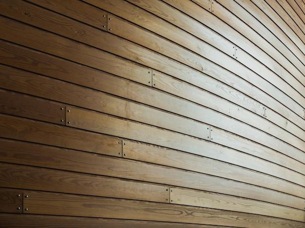 日光の下でそれに釘と木製の壁