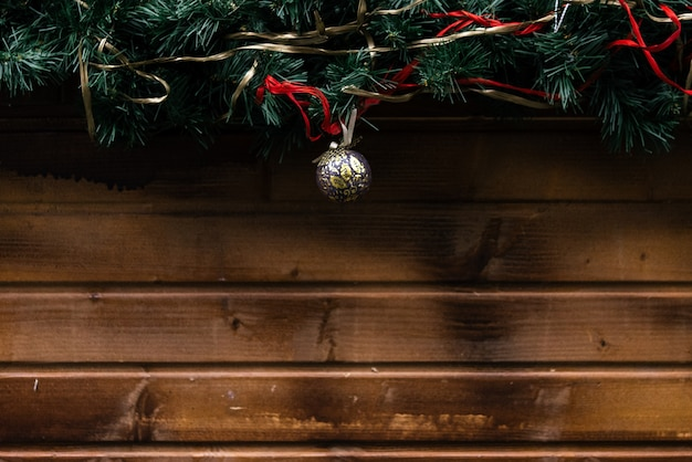 Wooden wall with a pine branch and christmas baubles