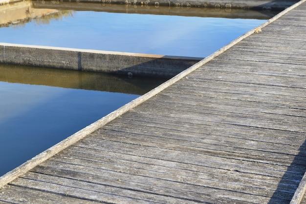 カキ養殖のための古い海水池を横切る木造の通路