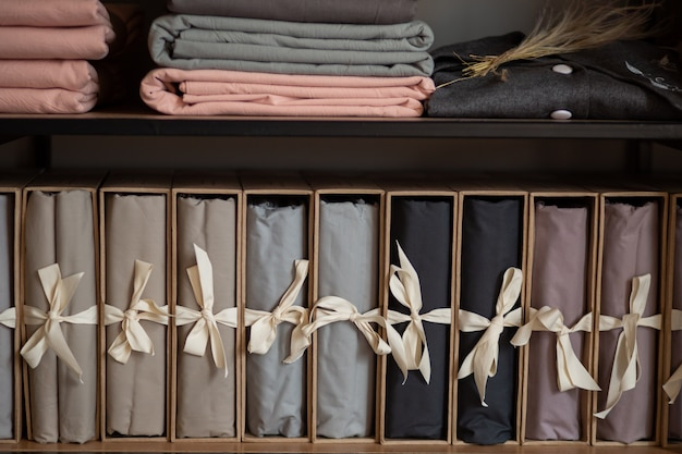 Wooden wardrobe with linens and clothes at home or in a store, design concept in the interior