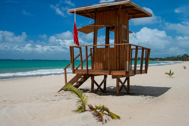 Деревянная сторожевая башня с красным флагом на песчаном пляже в пуэрто-рико