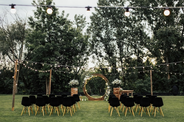 Wooden wedding arch decorated by white flowers with greenery standing in the center of wedding ceremony. black chairs on sides.
