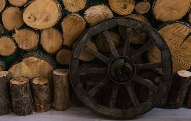 A wooden wheel stands near a wall of logs.