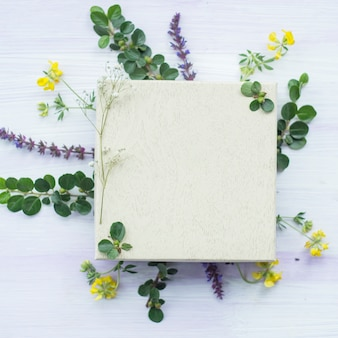 Wooden white blank frame under the flowers and leaves on textured background