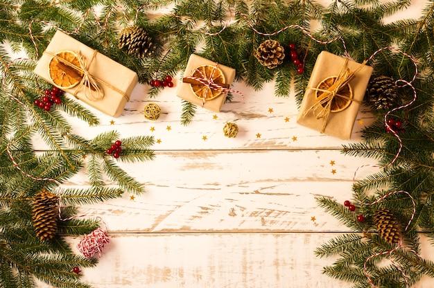 가문비나무 가지와 원뿔이 있는 나무 화이트 크리스마스 배경, 크래프트 종이에 있는 선물, 오렌지, 계피, 아니스 조각. 평면도.