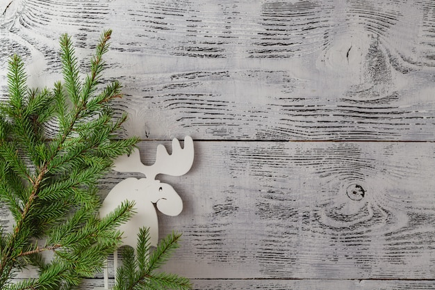Wooden white christmas deer decoration on wooden table. chistmas consept. top view