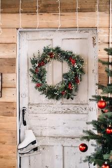 Деревянная белая дверь в дом, украшенный рождественским венком.