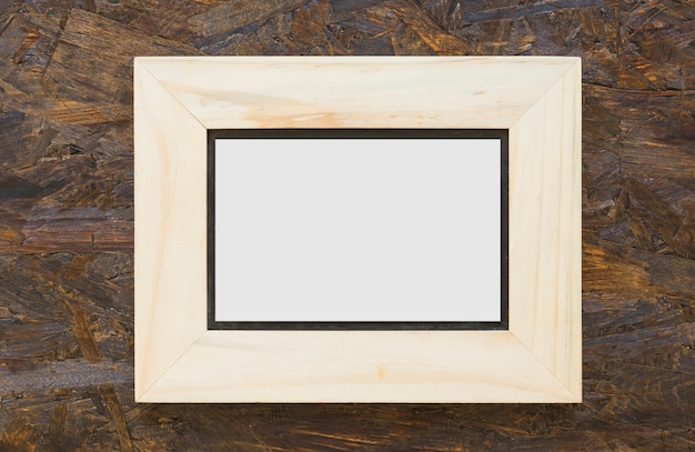 Wooden white frame on textured wooden backdrop