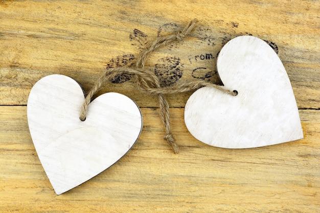 Деревянные белые сердца на деревянной поверхности