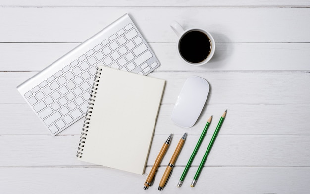 Wooden white office desk table with cup of coffee, notebook, pen on it.