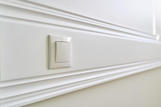 電源ソケットが付いている壁に接着される木の白い塗られたパネル板