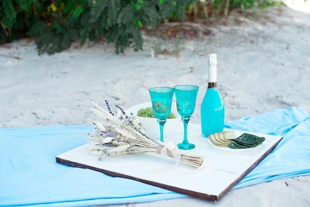 青いシャンパンのボトルとさまざまなチーズのプレート、季節限定のアウトドアやホリデーパーティーやピクニックのコンセプトを持つ木製の白いピクニック用のテーブル。