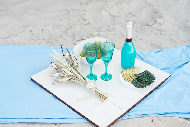 Wooden white picnic table with a bottle of blue champagne and plates with different cheeses, concept for a seasonal outdoor or holiday party or picnic.