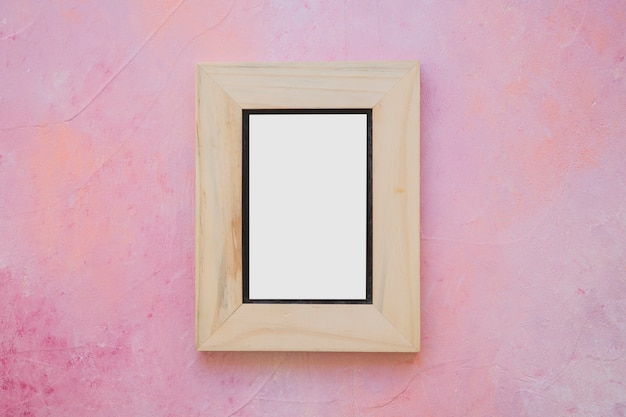 Wooden white picture frame on painted pink wall