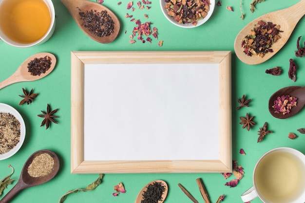 Wooden whiteboard surrounded with different types of herbs on green backdrop