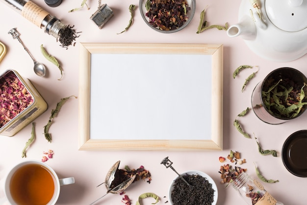 Wooden whiteboard surrounded with different types of herbs on white background