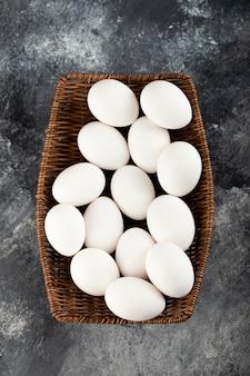Un vimini di legno pieno di uova di gallina crude bianche.
