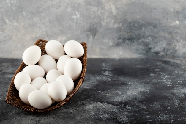A wooden wicker full of white raw chicken eggs .