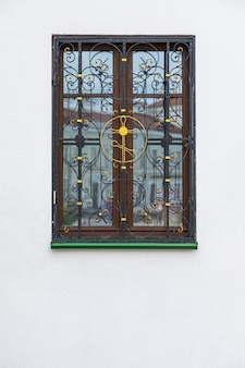 Wooden window with wrough iron cross