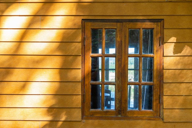 Wooden window on wooden wall with sunshine.
