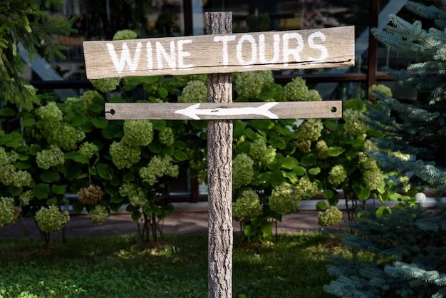 緑色の低木と矢印のある木製のワインツアーの標識
