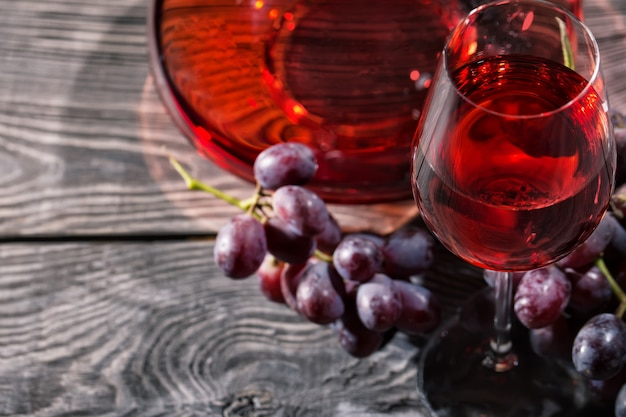 赤ワインのグラスとブドウの房を持つ木製