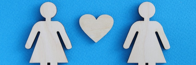 Wooden women between them heart on blue background.