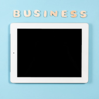 Wooden word business over the top of digital tablet against blue background