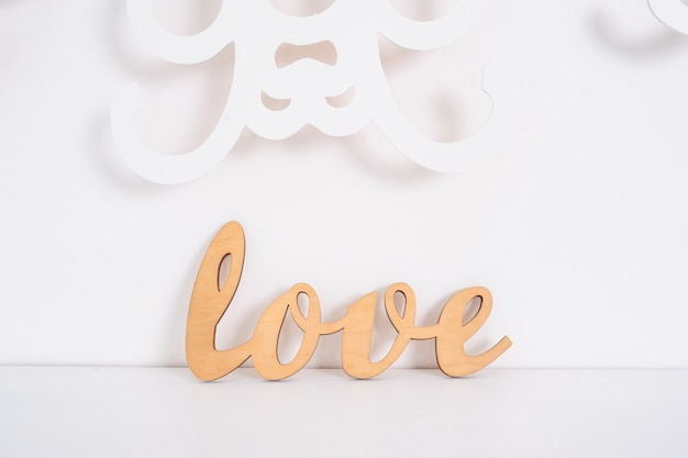 Wooden word love on white in studio